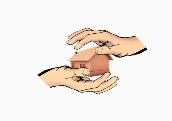 Twee handen rond een huis ter bescherming
